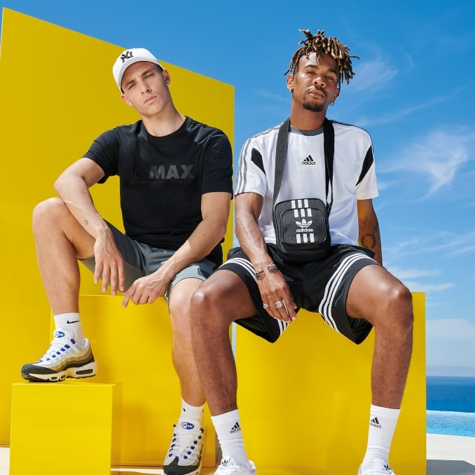 Dos hombres con ropa de verano, gorra NY y bandolera adidas Originals