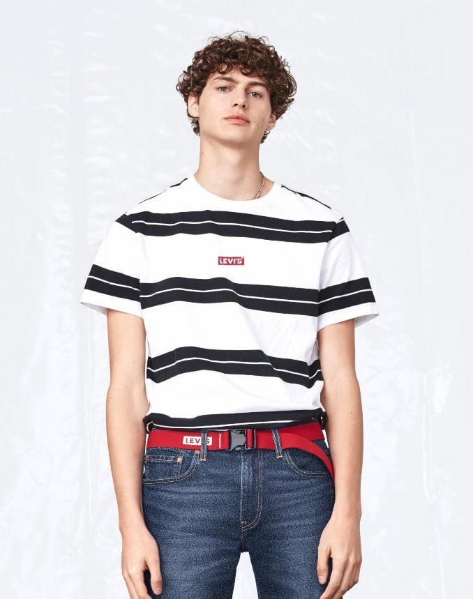 Joven con camiseta a rayas y pantalón vaquero, outfit de Levi's
