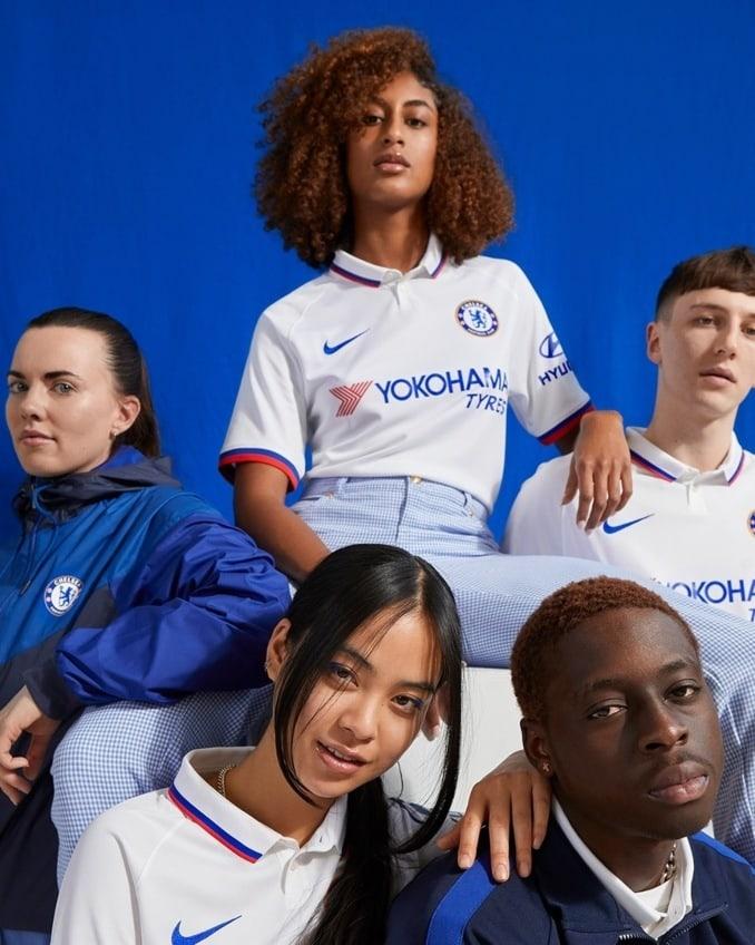 Grupo de hombres y mujeres con la segunda equipación 2019-20 del Chelsea FC